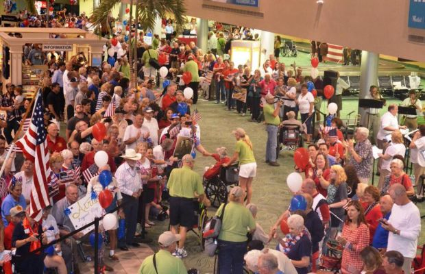 The author accompanies Bob through a crowd welcoming their soldiers home as someone reaches to shake his hand.