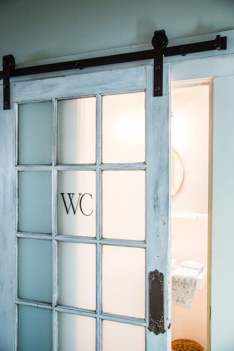 Sarah Karakarian's rustic French barn door repurposed into a bathroom door